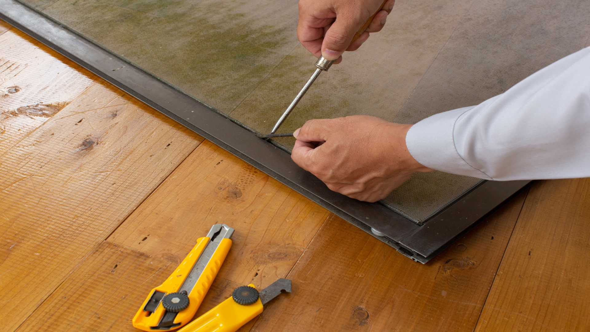 Man Repairing A Window Screen Screen Room Repair and Installation Gutter Solutions and Home Improvements Pensacola FL 850 776 1782