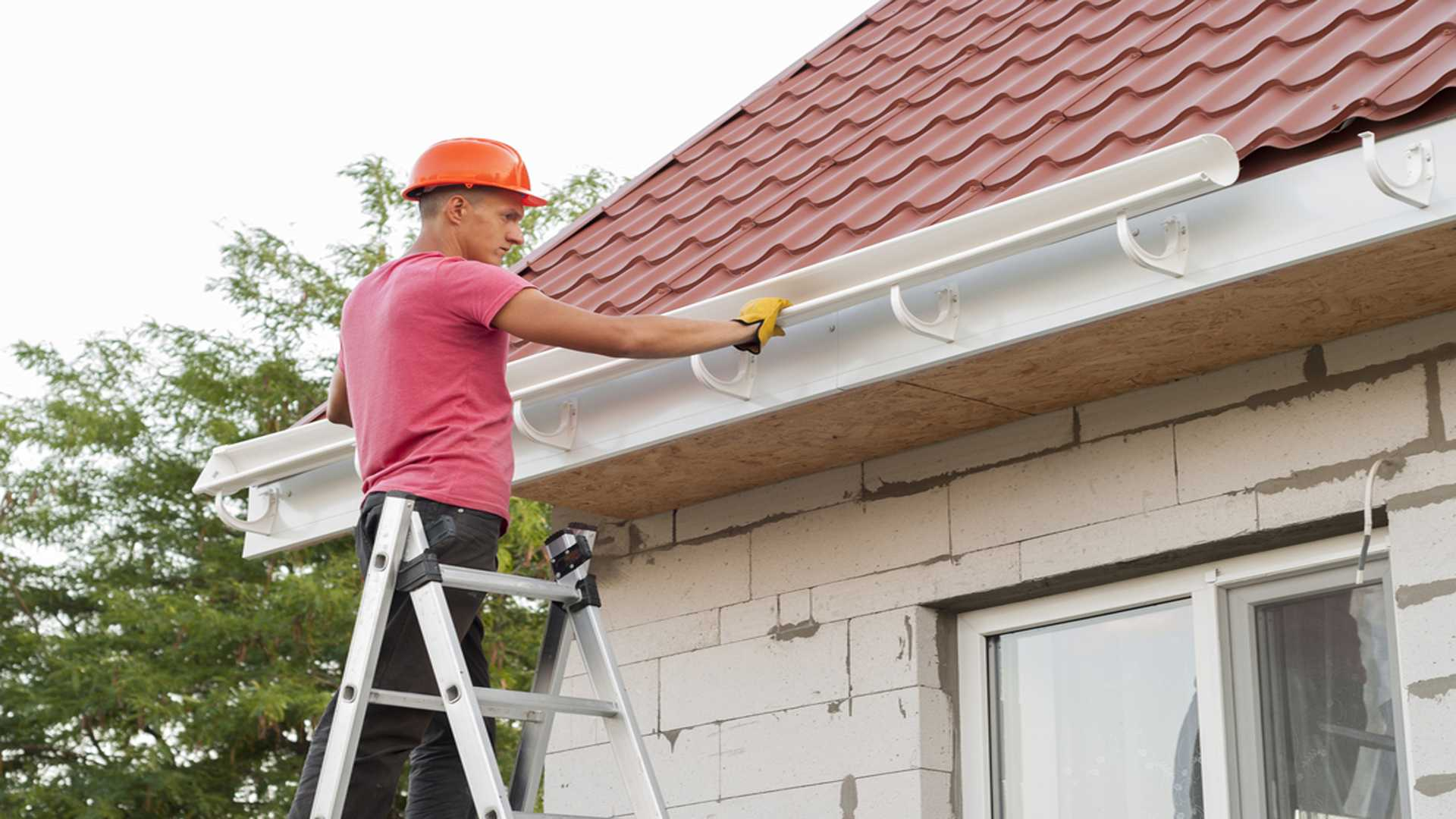 Worker Installing Gutter System On Roof Gutter Installation Gutter Solutions and Home Improvements Pensacola FL 850 776 178